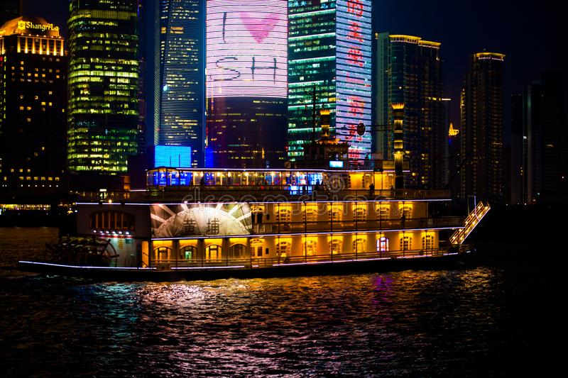 Paddlewheeler on Huangpu River and Skyscraper with advertise on the West Bank with Financal Center at night stock image