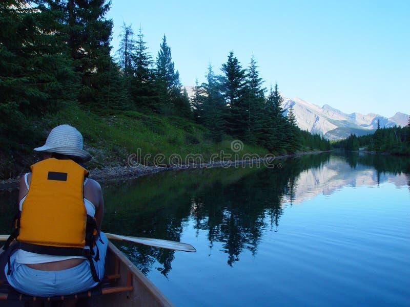 Paddling at dusk on a mountain lake royalty free stock image