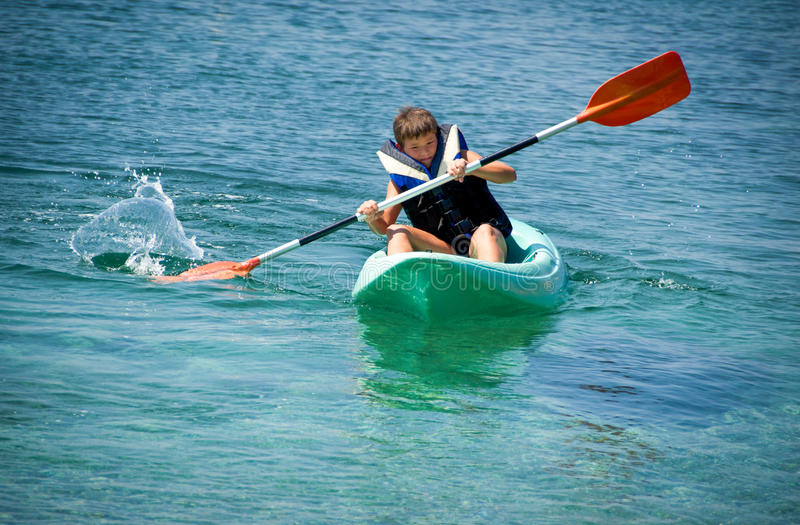 Paddling hard the kayak. Young boy paddling hard the kayak with splashes near the cliff at a clear day royalty free stock images