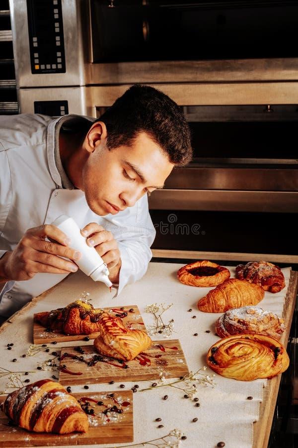 Padeiro de cabelo escuro que decora sobremesas da pastelaria para sua classe mestra fotografia de stock