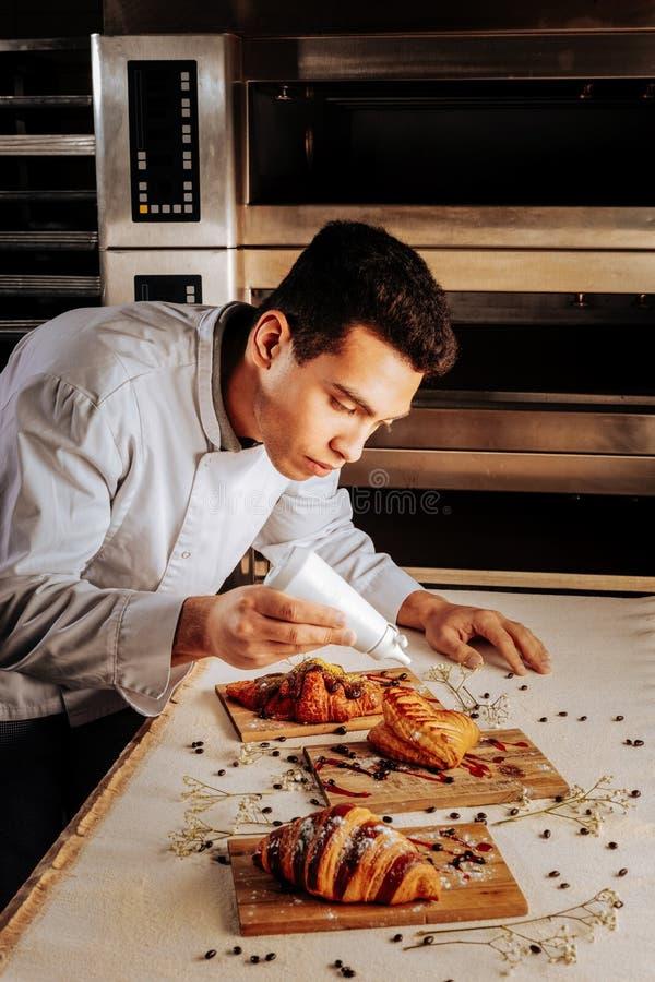 Padeiro de cabelo escuro que usa a morango que cobre para sobremesas da pastelaria fotos de stock