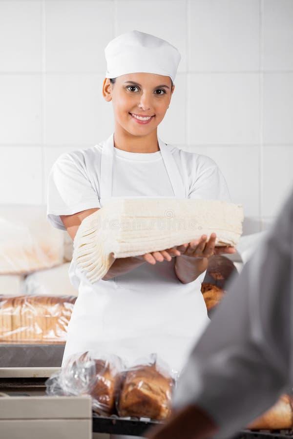 Padeiro de sorriso Holding Bread Slices na padaria imagens de stock
