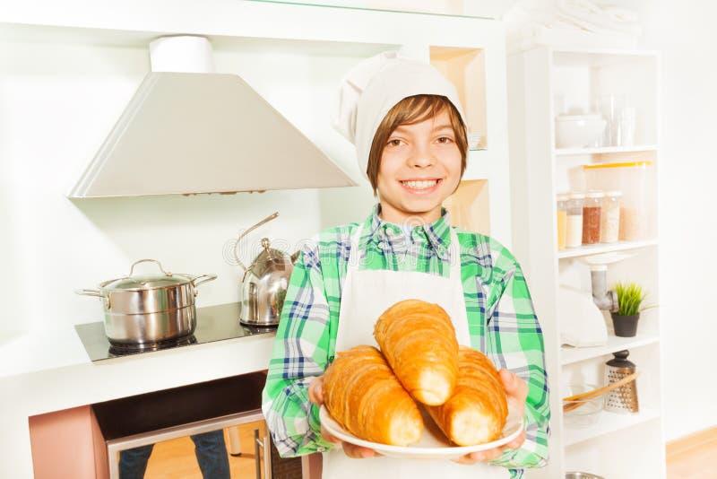 Padeiro de sorriso novo com a placa de croissant frescos fotos de stock