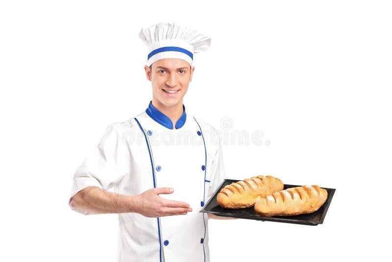 Padeiro de sorriso que mostra pães recentemente cozidos imagem de stock
