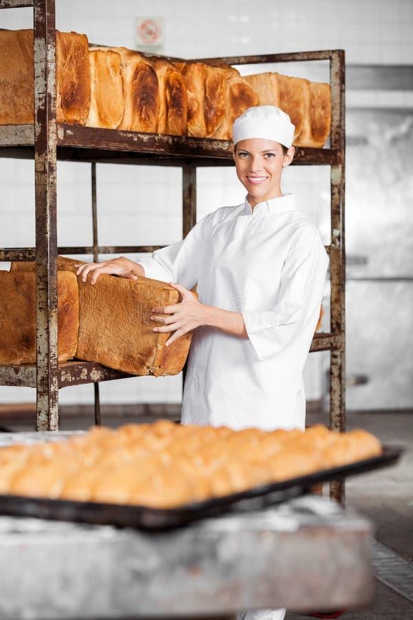 Padeiro fêmea novo Removing Bread Loaf da cremalheira fotografia de stock royalty free