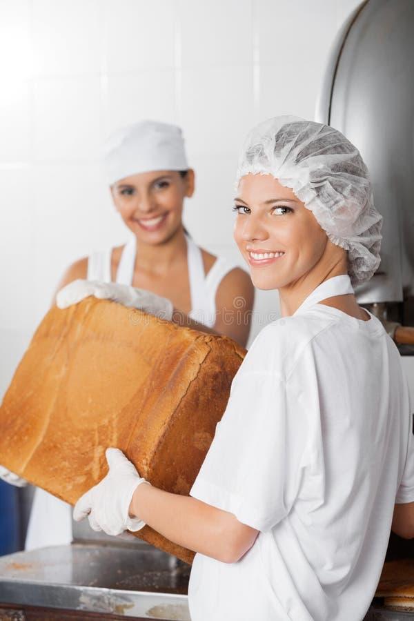 Padeiro fêmea seguro Holding Bread Loaf com colega de trabalho imagens de stock royalty free