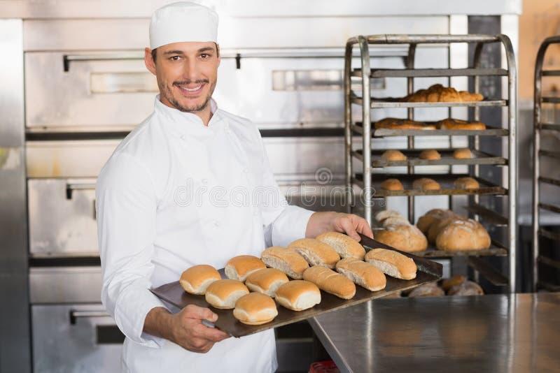 Padeiro feliz que mostra a bandeja de pão fresco fotografia de stock