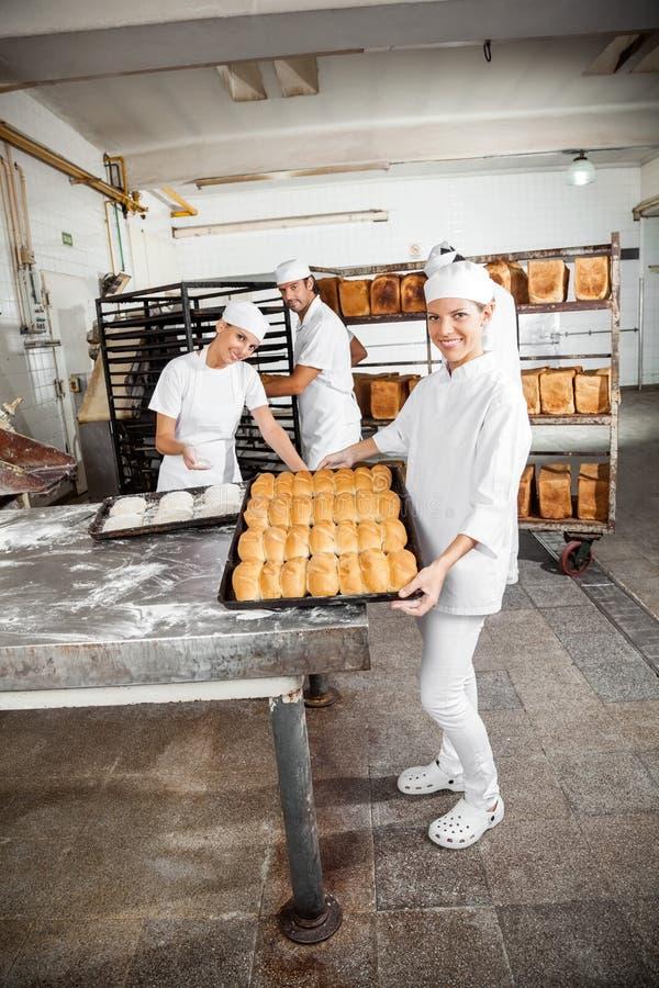 Padeiro feliz Showing Baked Breads na padaria imagens de stock