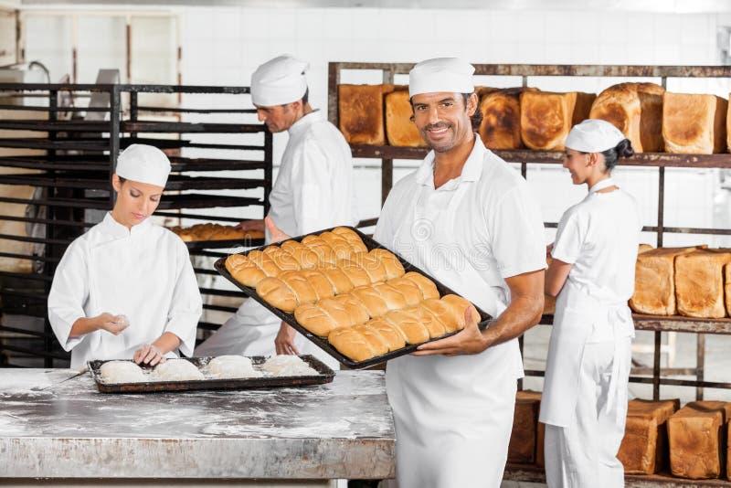 Padeiro meados de Showing Baked Breads do homem adulto na padaria fotografia de stock