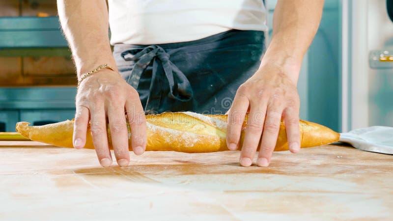 Padeiro que guarda o pão fresco para rasgá-lo em uma metade As mãos masculinas guardam o baguette fotografia de stock