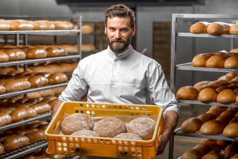 Padeiro que guarda pães na fabricação imagens de stock royalty free