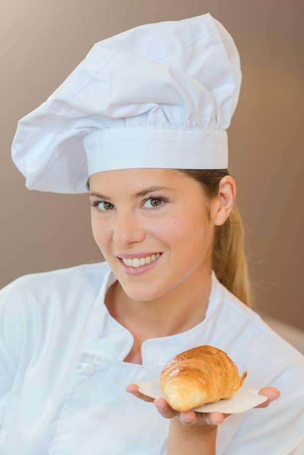Padeiro que guarda um croissant imagens de stock