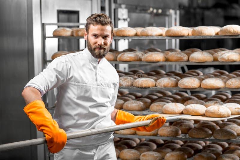 Padeiro que põe com os loafs do pão da pá na fabricação imagens de stock royalty free