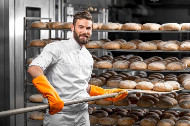 Padeiro que põe com os loafs do pão da pá na fabricação imagens de stock