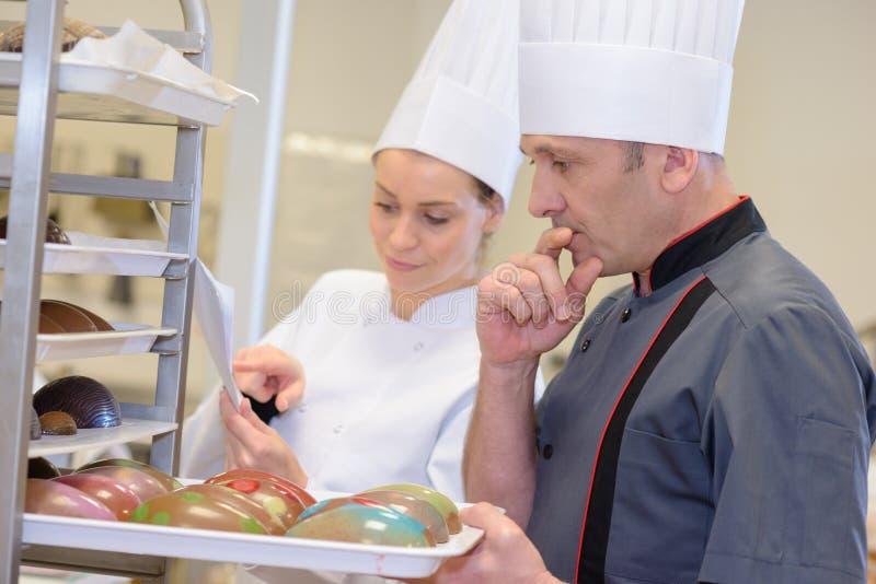 Padeiros seguros do retrato que embalam pastelarias na padaria imagem de stock royalty free