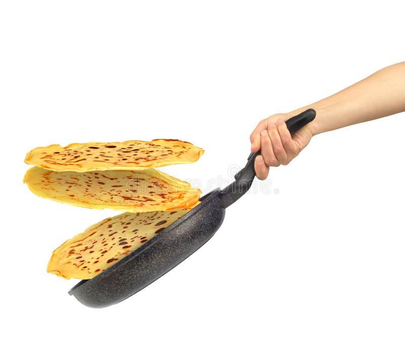 Padella con i pancake di volo in mano delle donne immagine stock