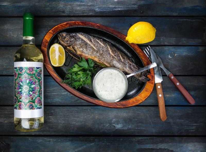Padella con il pesce saporito della trota su fondo di legno con una bottiglia dei verdi, della salsa e del limone del vino fotografia stock libera da diritti