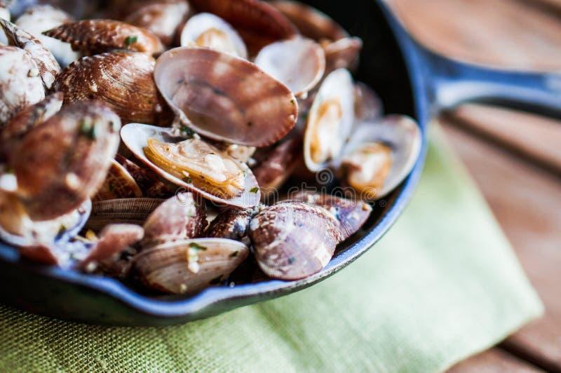 Padella del ghisa delle vongole di vapore fresche deliziose con aglio a fotografia stock