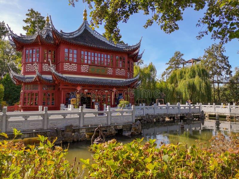Padiglione del tè nel colore rosso tradizionale con i fasci di tetto blu nel giardino cinese nel parco Pairi Daiza della fauna se immagine stock