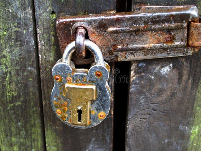 Padlock. Old rusty padlock on a decaying fence stock photo