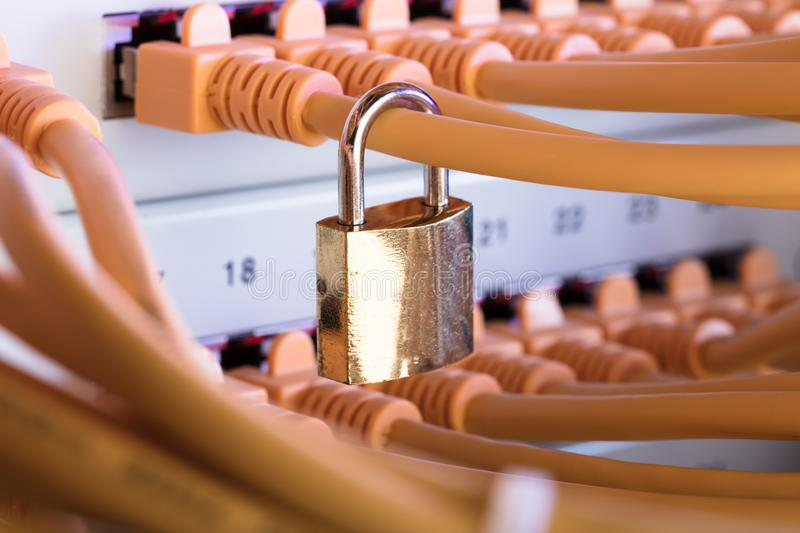 Padlock Attached To Network Cable In Server Room. Closeup of padlock attached to network cable in server room stock photos