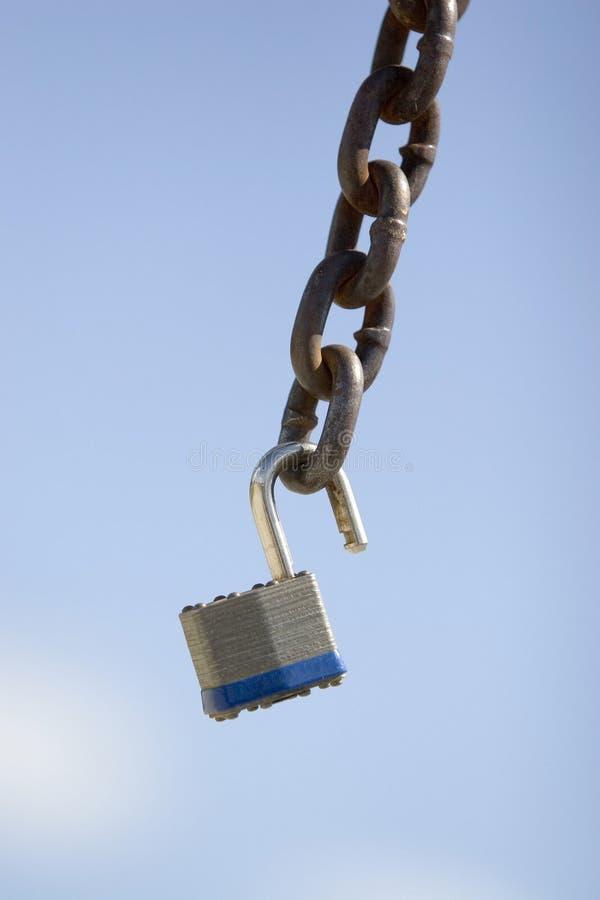 Padlock on chain. Padlock dangling on chain against blue sky stock photo