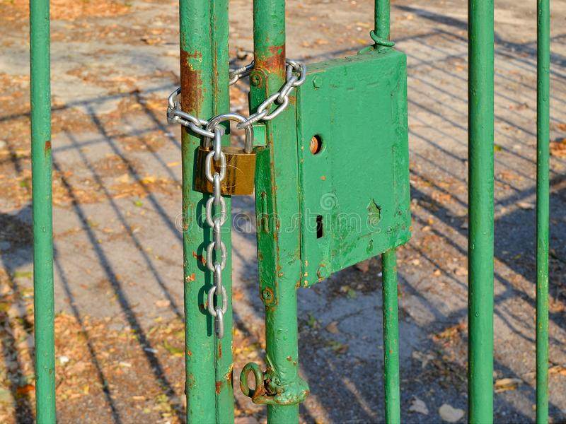 Padlock with a chain closes the old rusted metal gates, painted with green color royalty free stock image