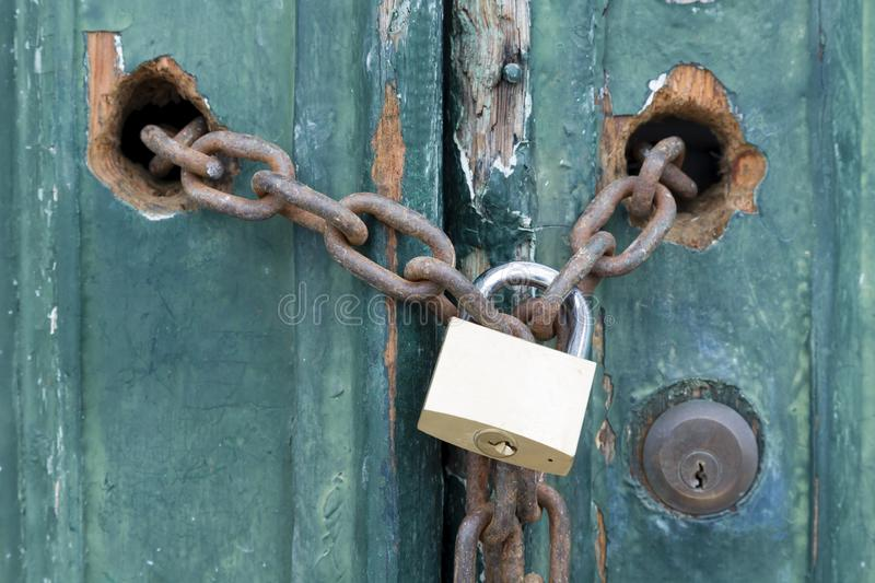 Padlock and chain. On an old door, illustrating concepts of security and encryption royalty free stock photography