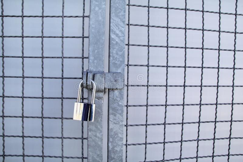 Padlock on a chainlink fence / Master key and old rusty chain with steel cage, close up / Closed lock with chain on metal fence. royalty free stock photography