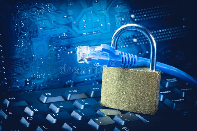 Padlock with ethernet network cable close up against blue circuit motherboard background. Internet data privacy information securi stock photos