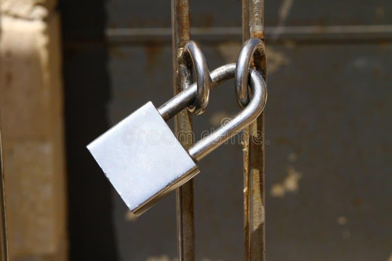 Padlock on gate. Shiny padlock secures a metal gate royalty free stock photography