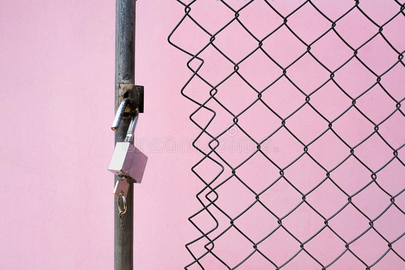 a padlock and a key at the wired gate royalty free stock photography