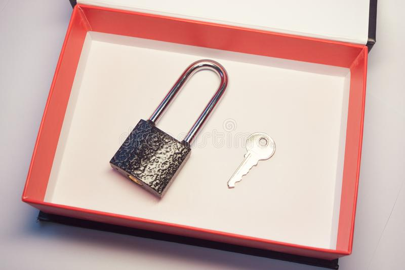 Padlock and the keys to it in a box with red cardboard margins stock photography
