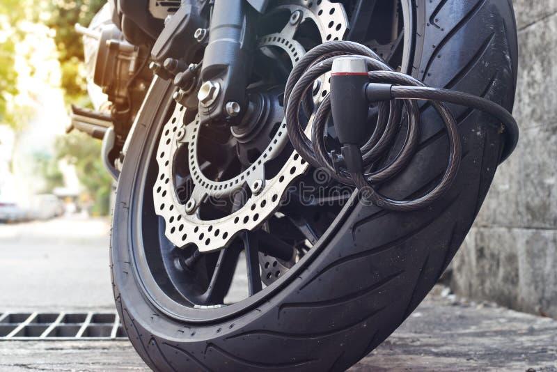 Padlock la serrure de sécurité bloquant la roue de moto sur la rue, système anti-vol images stock