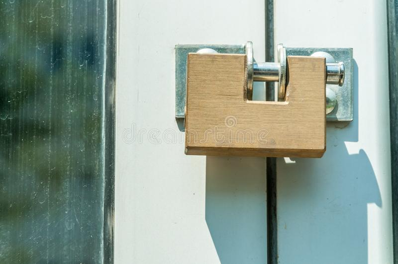 Locked golden modern steel safety or security padlock on the entrance doors close up royalty free stock image