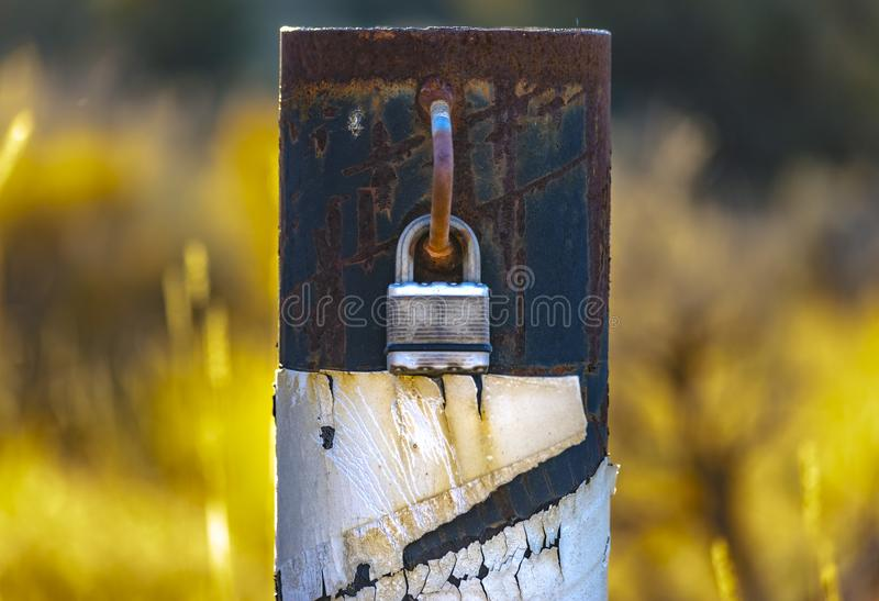 Padlock on a metal pole to lock road access. Of a trail in Eagle Mountain, Utah. The pole is the other side of the gate and the lock keeps the pole from being stock image
