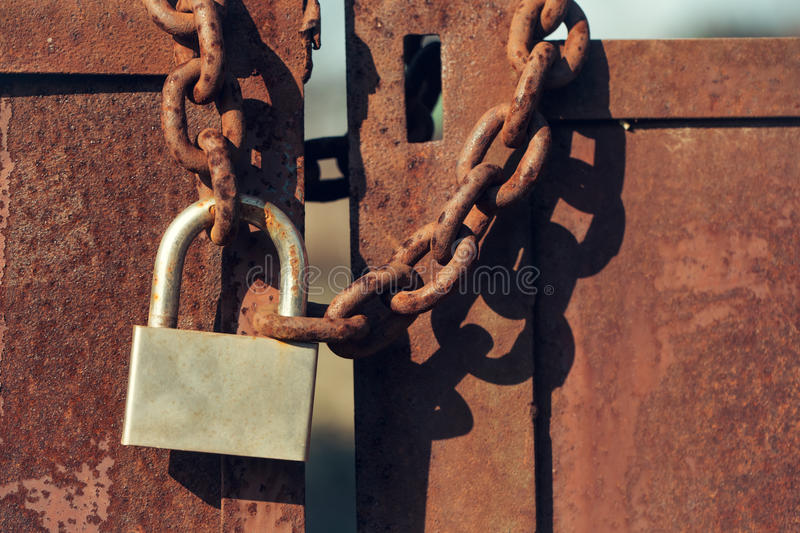 Padlock on rusty gate doors. Padlock with shackle and locking mechanism closeup one portable lock on chain on unpainted rusty metal gate doors outdoor on blurred royalty free stock photography