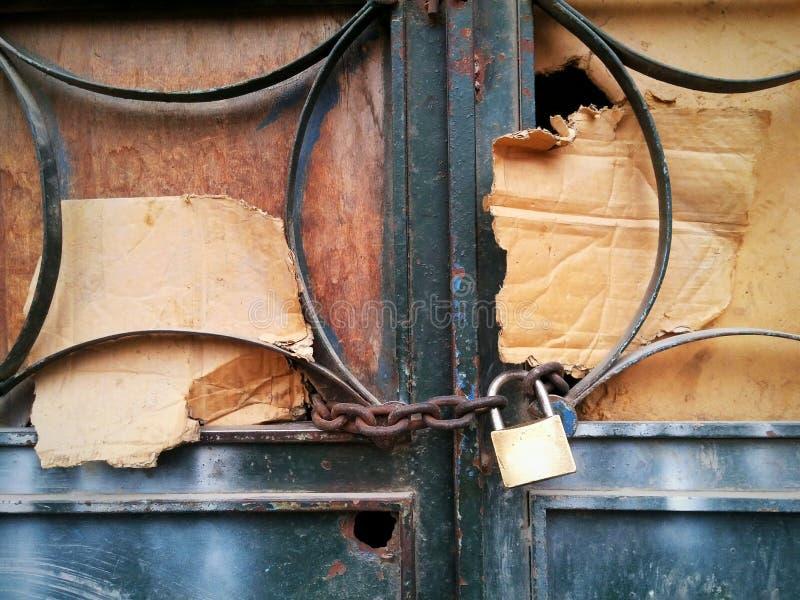 Padlocked ha incatenato la porta del ferro del cartone fotografie stock libere da diritti