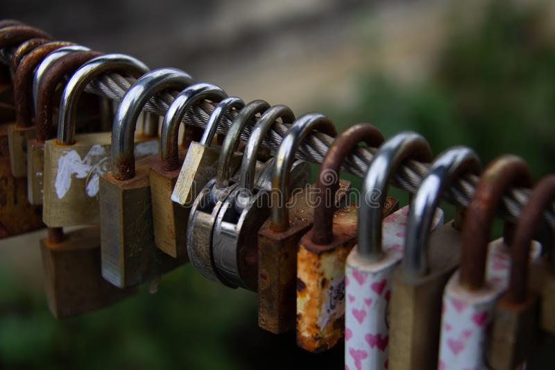 Padlocks, love lock on a bridge as a sign of connection. Cables and fences on bridges used for locks padlocks. Couples bond their relation with a love lock as stock photos