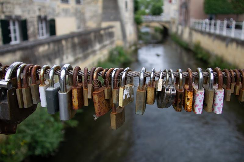 Padlocks, love lock on a bridge as a sign of connection. Cables and fences on bridges used for locks padlocks. Couples bond their relation with a love lock as stock images