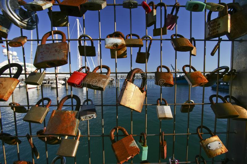 Padlocks of love on welded wire fence at marina with sailboats in Silo Park, Auckland, New Zealand royalty free stock photography