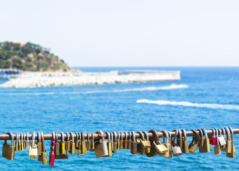 Padlocks on rope, blue sea background royalty free stock photo