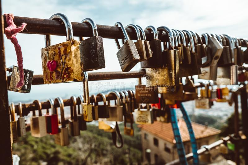 padlocks on rusty bar with blurred view of Barcelona from Tibidabo mountain on sunny summer day stock photo