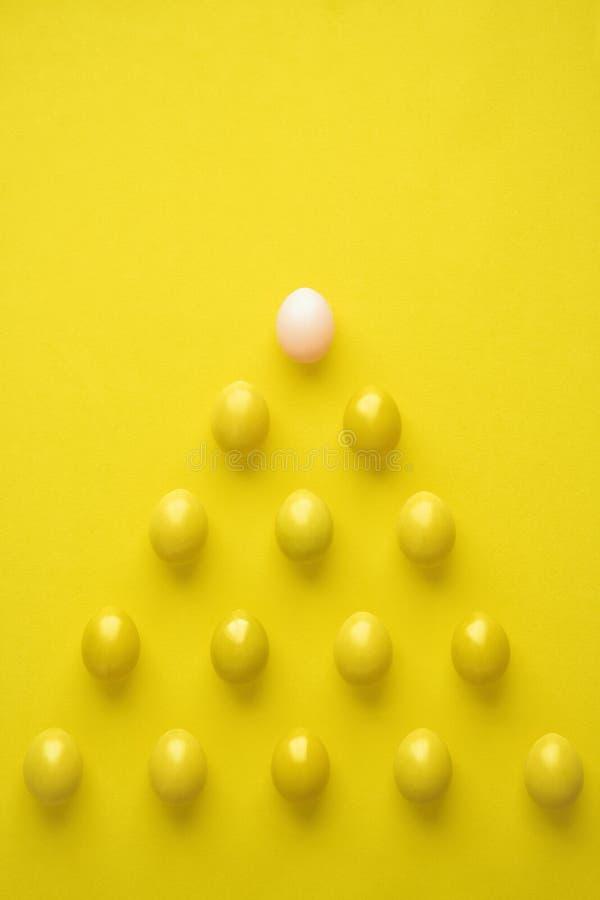 Padrões De Ovos De Galinha Em Forma De Pirâmide Contra Fundo Amarelo fotos de stock