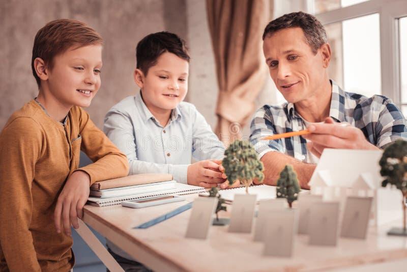 Padre adoptivo sonriente que siente alegre pasando tiempo con los ni?os foto de archivo