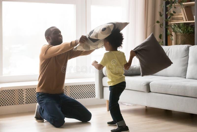 Padre africano e piccolo combattimento del figlio che giocano con i cuscini fotografia stock libera da diritti