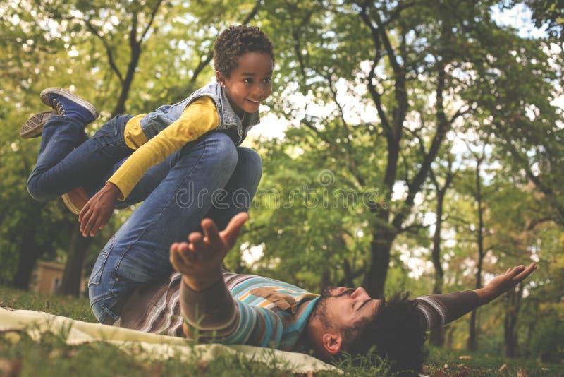 Padre afroamericano che gioca con sua figlia in idromele immagini stock libere da diritti