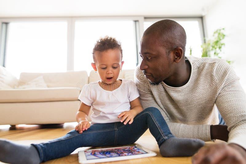 Padre afroamericano con la piccola figlia con la compressa a casa immagini stock