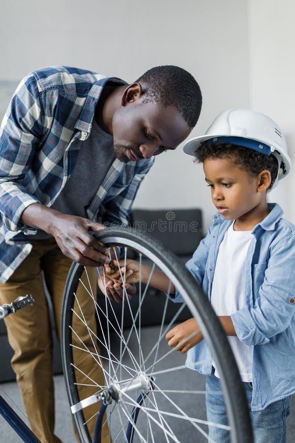 padre afroamericano e piccolo figlio in elmetto protettivo immagine stock libera da diritti