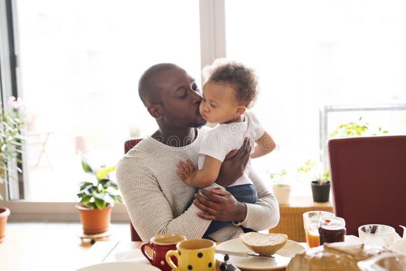 Padre afroamericano giovane con sua figlia che mangia prima colazione immagini stock